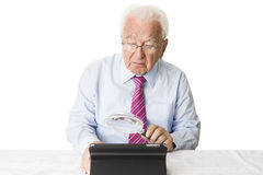 Senior with tablet and magnifying glass. Senior using a tablet computer with a magnifying glass Stock Photos