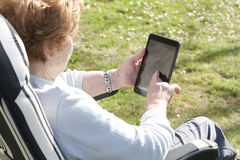 Senior with tablet. Senior woman with mobile tablet outdoors Royalty Free Stock Image