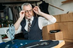 Senior tailor wearing glasses for sewing. At sewing workshop stock photo