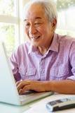 Senior Taiwanese man working on laptop Stock Images
