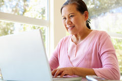 Senior Taiwanese woman working on laptop Stock Photo