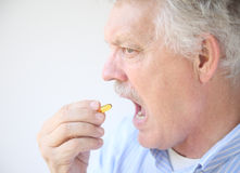 Senior takes fish oil supplement Stock Photo