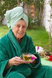 A senior takes her tisane in an open air spa studio. A smiling senior woman between 70 and 80 years old is taking a cup of tisane before going through skin care Stock Image