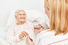 Senior takes a medicine with water. Sick elderly women lies in bed and takes a medicine with water Stock Photography