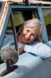 Senior Taking a Drive. Smiling senior taking a cruise in the old rustbucket Royalty Free Stock Photo