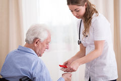 Senior taking medications. Pensioner taking his daily dose of pills stock image