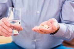 Senior taking overdoses pills at home. Old man taking overdoses medicaments at home Stock Photography