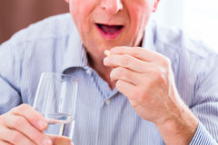 Senior taking overdoses pills at home Stock Photography
