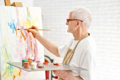 Senior talented painter while painting his masterpiece at studio. Side view of senior talented painter while painting his masterpiece at bright art studio stock photo