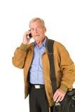 Senior talking on his smartphone. Senior man travelling and talking on his smartphone Royalty Free Stock Photo
