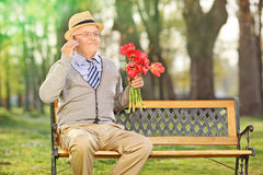 Senior talking on phone and holding red tulips Stock Images