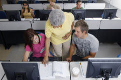 Senior Teacher Assisting Students Royalty Free Stock Images