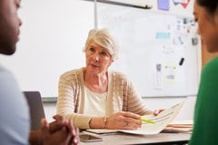 Senior teacher at desk talking to adult education students Stock Photos