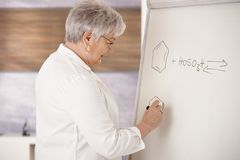 Senior teacher drawing on whiteboard Stock Images