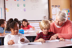 Senior teacher helping elementary school pupil in class Royalty Free Stock Photos