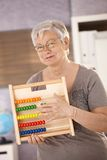 Senior teacher holding abacus. Senior teacher standing in classroom, holding abacus, smiling stock photography