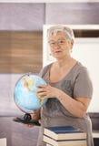Senior teacher holding globe. Senior teacher standing at desk, holding globe, teaching geography in elementary school royalty free stock photo