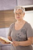 Senior teacher holding textbook. Portrait of senior teacher standing in classroom, holding textbook, looking at camera Royalty Free Stock Photo