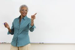 Senior teacher pointing while gesturing against white board in classroom Stock Image