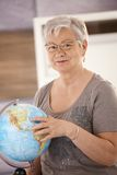 Senior teacher pointing at globe. Senior teacher standing at desk, pointing at globe, teaching geography in elementary school stock photos