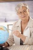 Senior teacher pointing at globe. Senior teacher sitting at desk, pointing at globe, teaching geography in elemantary school Stock Photography