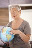 Senior teacher pointing at globe Stock Image