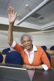 Senior Teacher Raising Hand. Portrait of a senior teacher raising hand in classroom stock images