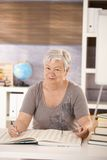 Senior teacher in school searching in a book. Portrait of senior teacher sitting at desk in classroom, searching in a book, looking at camera royalty free stock photo