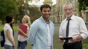 Senior teacher and student looking at camera, higher education opportunities. Stock photo royalty free stock images