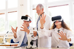 Senior teacher teaching biology to high school students. Senior teacher teaching biology to his high school students with virtual reality glasses in laboratory stock photography