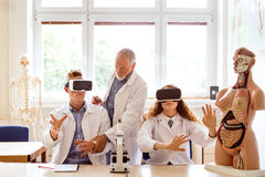 Senior teacher teaching biology to high school students in labor. Senior teacher teaching biology to his high school students with virtual reality glasses in royalty free stock photos