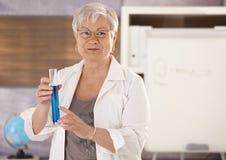 Senior teacher teaching chemistry. Senior teacher standing in classroom, holding test tube, teaching chemistry in elemantary school stock photos