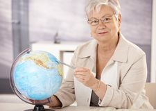 Senior teacher teaching geography. Senior teacher sitting at desk, pointing at globe, teaching geography in elementary school stock photography