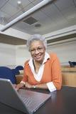 Senior Teacher Using Laptop At Desk. Portrait of a happy senior teacher using laptop at desk royalty free stock photo