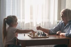 Senior teaches a child to play chess. People are sitting at a table by the window. On the table a chessboard with pieces.