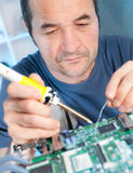 Senior tech fixes computer circuit board Stock Photos