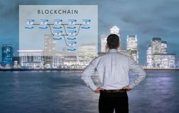 Senior technologist looking at blockchain illustration. Blockchain schematic on glass panel with senior technology executive looking at the chart with London in Royalty Free Stock Image