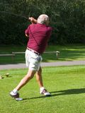 Senior Tee Off. A senior man tees off on a summer afternoon royalty free stock images