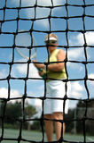 Senior tennis. An active senior woman on the tennis court as seen through the net (focus on net stock photo