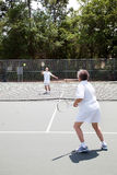 Senior Tennis Match. Senior man and woman playing in a tennis match Royalty Free Stock Photos