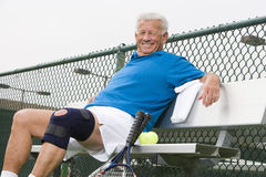 Senior Tennis Player Relaxing On Bench Royalty Free Stock Images