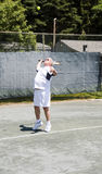 Senior tennis player serving ball. Handsome middle age male tennis player serving with ball in air on tennis court at club Stock Image