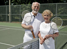 Senior Tennis Players. A happy senior couple stays active by playing tennis stock image