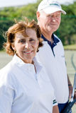 Senior tennis players. Close up of a pair of senior male and female tennis players holding racquets Stock Image