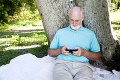 Senior Texts on Smart Phone Stock Image