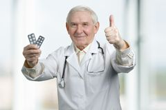 Senior therapist with two packs of medicine. royalty free stock photo