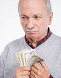 Senior thoughtful man holding dollar bills Royalty Free Stock Photos