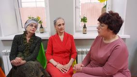 Elderly women sit and talk on friend meeting in pensioners club. stock video
