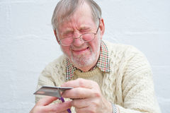 Senior tortured by cutting up card. Royalty Free Stock Photos