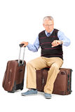 Senior tourist checking the time seated on his luggage. Isolated on white background Stock Photos